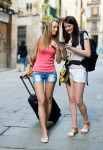 Two european students on vacation with luggage and using the map