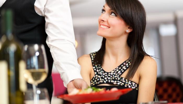 Сервитьор сервира на млада дама в ресторант